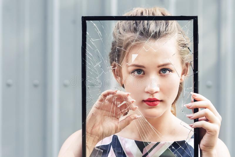 Beautiful teen girl holding broken glass in her hands. concept feminism. stock photography