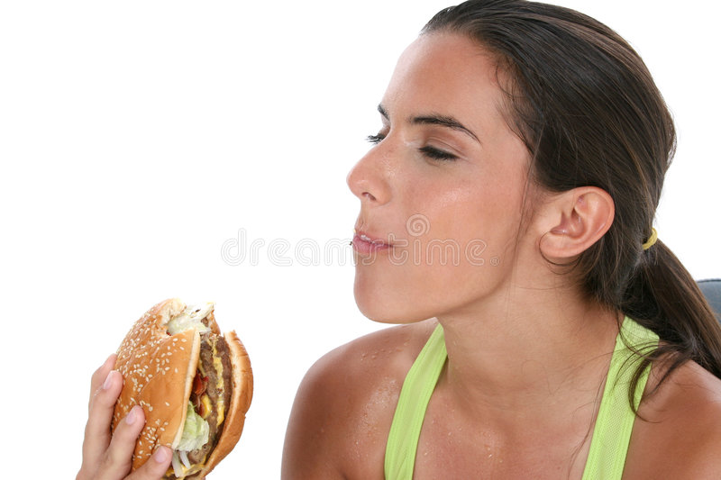 Beautiful Teen Girl Holding Colorful Weights And A Giant Cheeseburger royalty free stock images