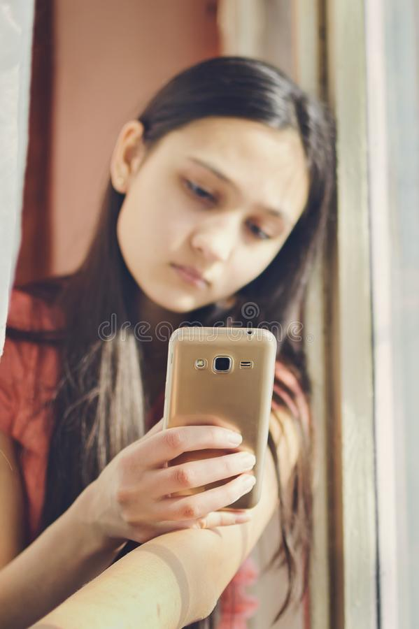 Beautiful teen girl holding a mobile phone. Lifestyle style. Close-up stock image