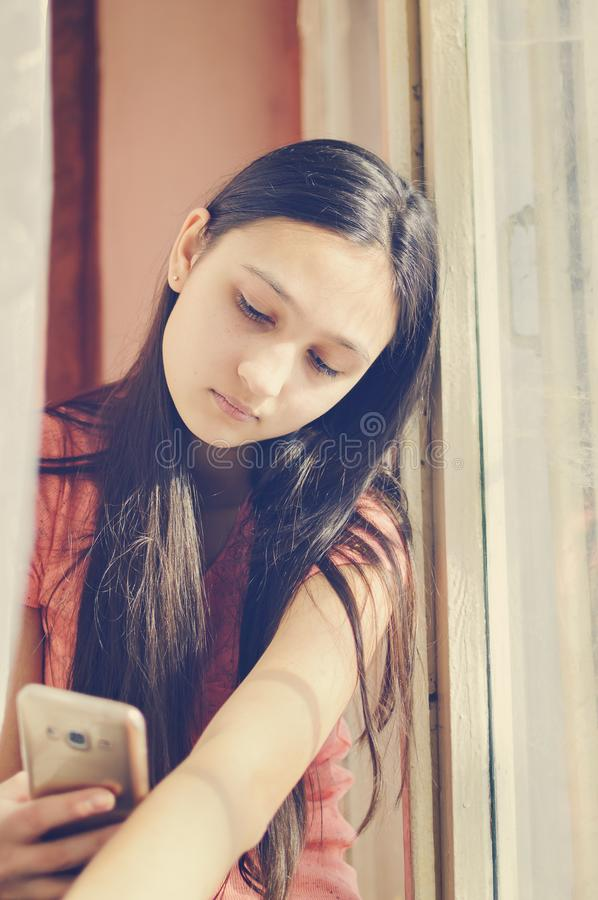 Beautiful teen girl holding a mobile phone. Lifestyle style. Close-up royalty free stock photos