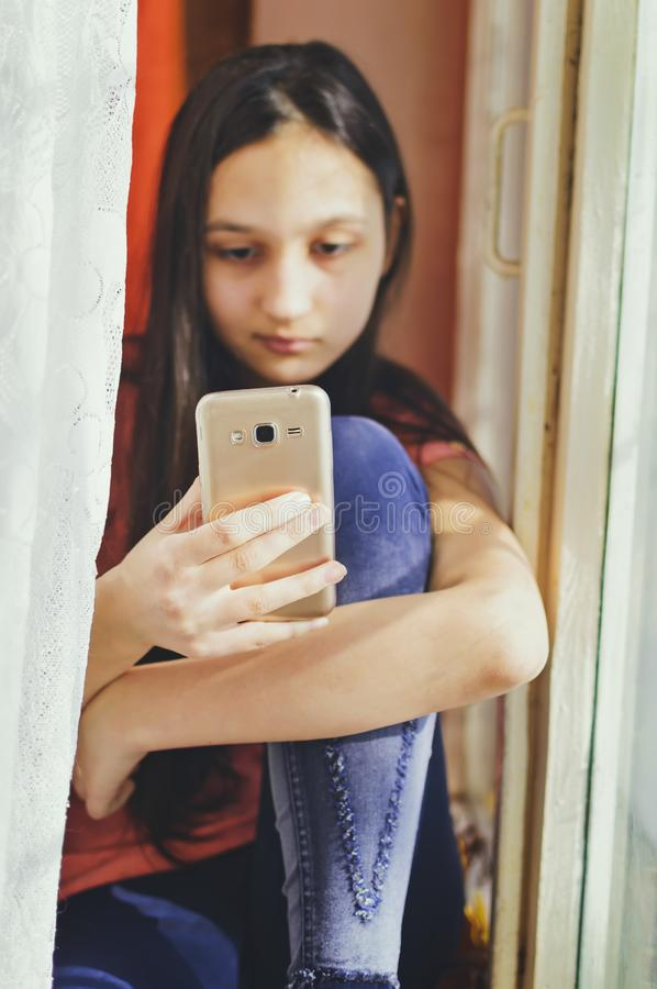 Beautiful teen girl holding a mobile phone. Lifestyle style. Close-up stock photos