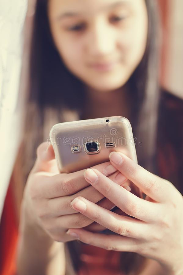 Beautiful teen girl holding a mobile phone. Lifestyle style. Close-up royalty free stock image