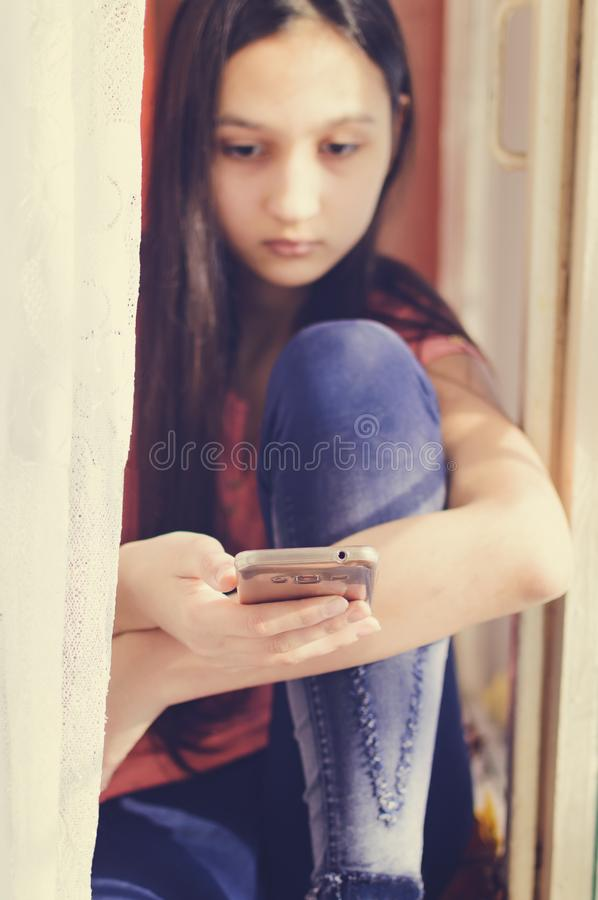 Beautiful teen girl holding a mobile phone. Lifestyle style. Close-up royalty free stock photo