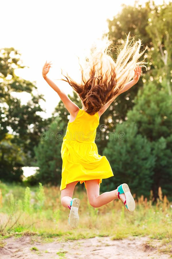 Beautiful teen girl Is jumping outside at summer sunset stock photos