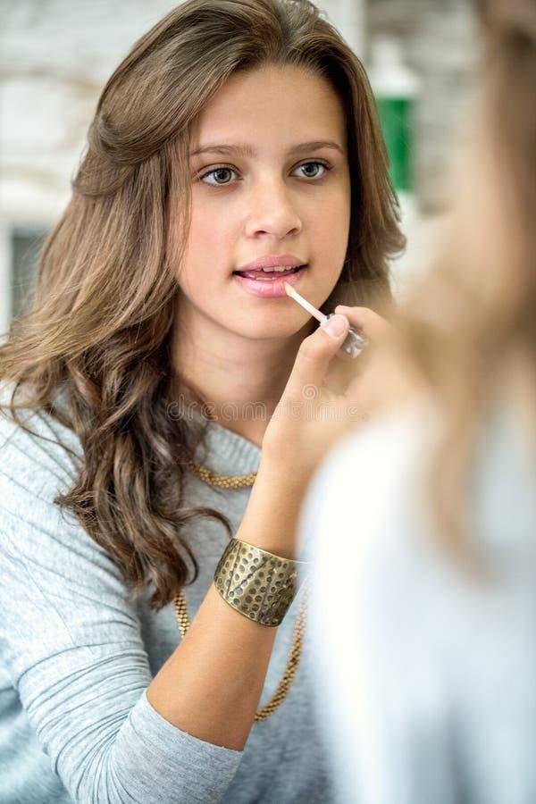 Beautiful teen girl with lip gloss. Beautiful teenager girl with lip gloss front of mirror stock images