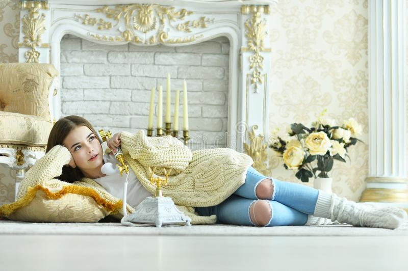 Beautiful teen girl lying on floor and talking on vintage phone stock images