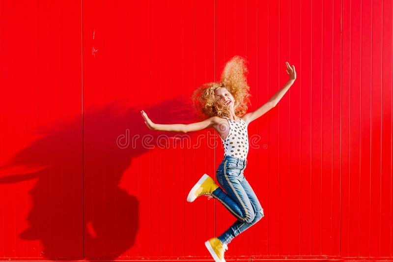 Beautiful teen girl makes a jump against the background of a red wall royalty free stock photos