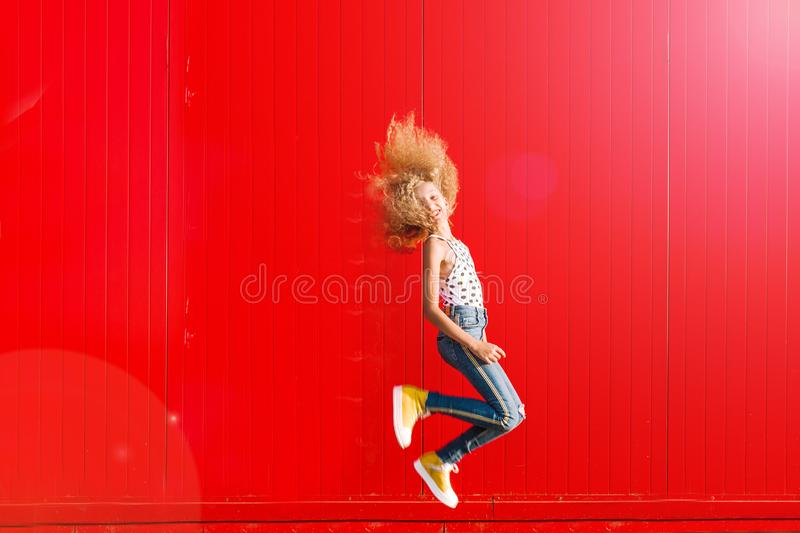 Beautiful teen girl makes a jump against the background of a red wall stock photo