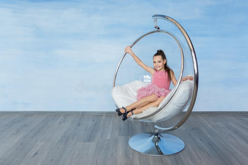 Beautiful teen girl in a pink dress sitting in on round glass chair on a blue background. stock photos