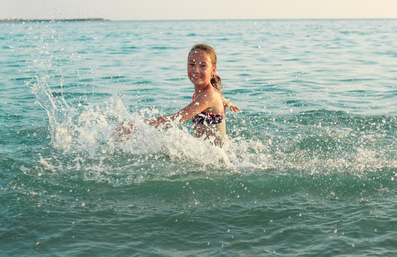 Beautiful Teen Girl playing In Sea Waves. Jump Accompanied By Water Splashes. Summer  Day, Happy childhood, Ocean Coast concept royalty free stock photos