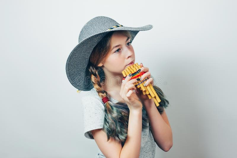 Beautiful teen girl in round hat playing  a pan flute. royalty free stock photography
