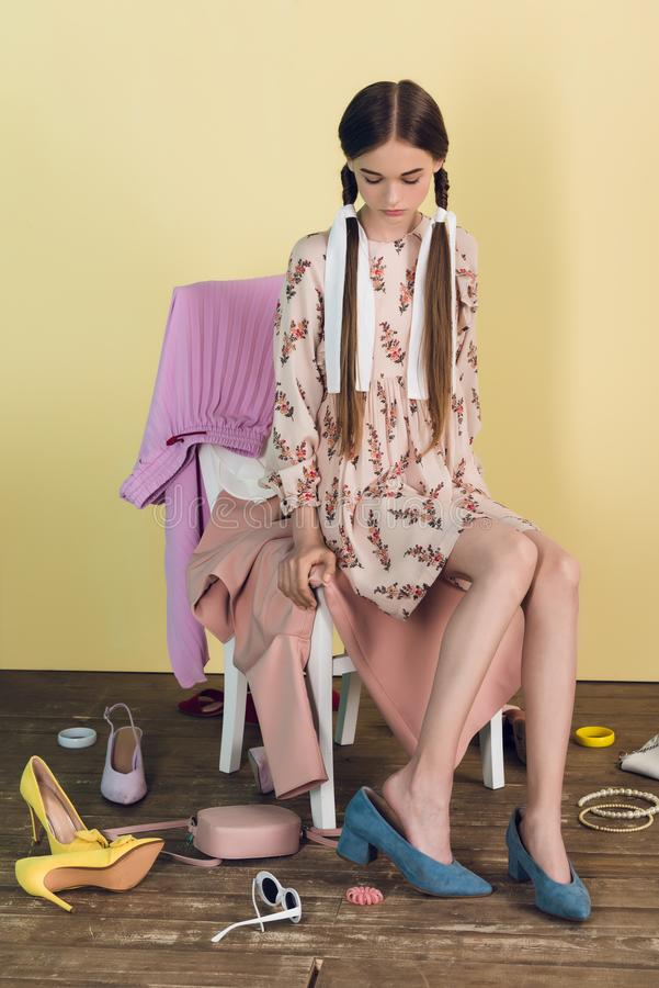 beautiful teen girl sitting on chair with mess of shoes stock photos