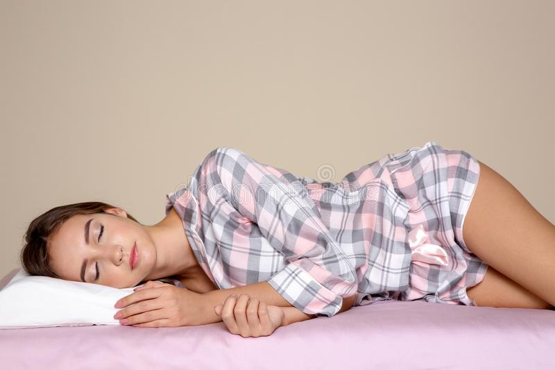 Beautiful teen girl sleeping with orthopedic pillow on bed. Against color background stock photo