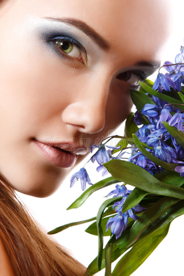 Beautiful teen girl smell and enjoy fragrance of snowdrop flower