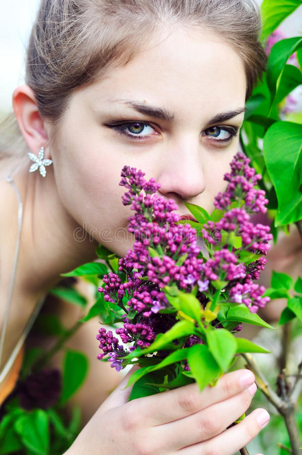 Beautiful teen girl smelling lilac blossoms stock photos