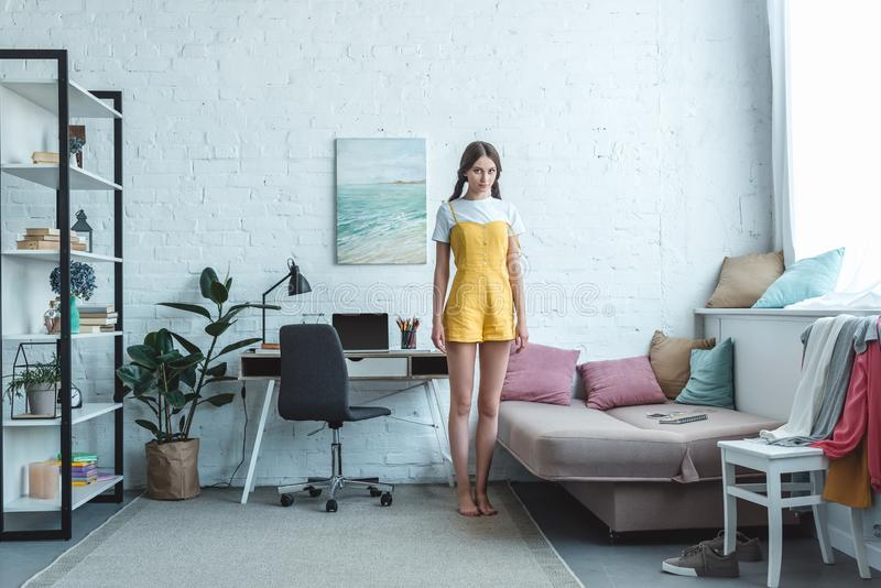 Beautiful teen girl standing in living room with sofa bookshelf and laptop. On table royalty free stock photo