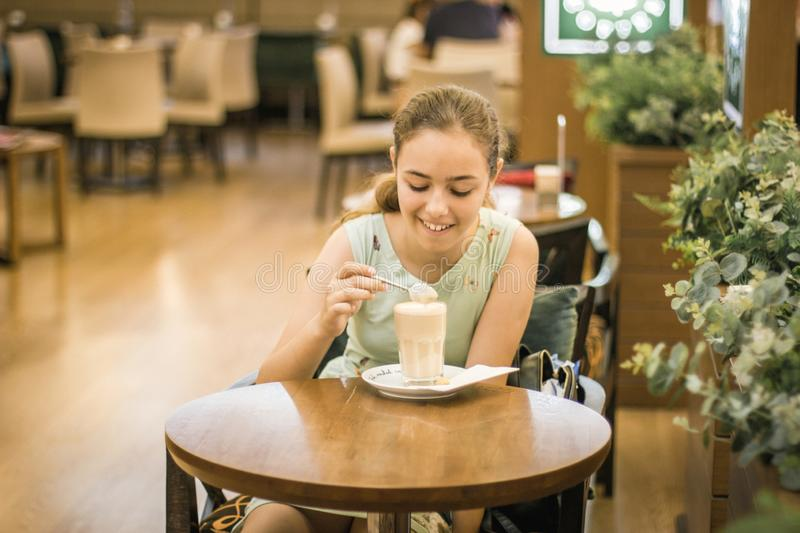 Beautiful teen girl stirring cream in coffee in tall glass at cafe royalty free stock photography