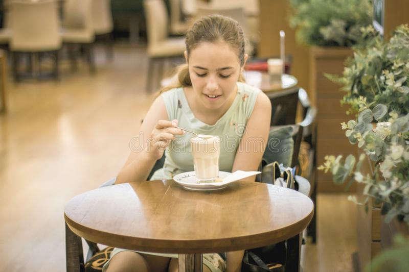Beautiful teen girl stirring cream in coffee in tall glass at cafe royalty free stock images