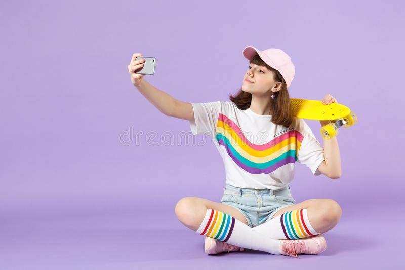 Beautiful teen girl in vivid clothes holding yellow skateboard, doing selfie shot on mobile phone isolated on violet royalty free stock image