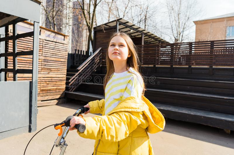 Beautiful teen girl in a cityscape with a scooter. Beautiful teen girl in a yellow sweatshirt and a yellow jacket in a cityscape with a scooter. Bright sunlight stock photography