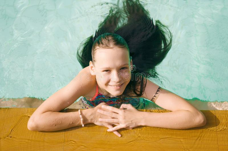 Beautiful teen irk relax in swimming pool in Thailand. Look up in camera. Top view. Beauty, vacation, healthy lifestyle royalty free stock image