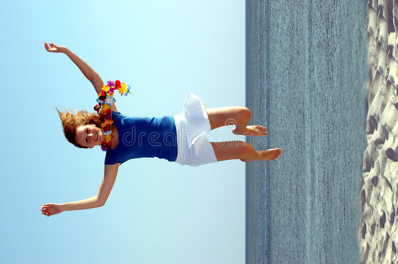 Beautiful teen jumping beach royalty free stock photography