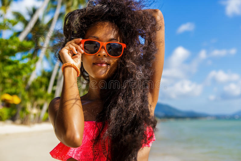 Beautiful teenage black girl in blue skirt and pink bra on the b. Outdoor lifestyle portrait of black lady in pink bra. Tanned hipster woman smile and correct royalty free stock photos