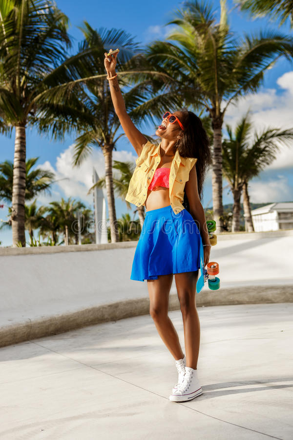 Beautiful teenage black girl in blue skirt take selfie with her. Outdoor lifestyle portrait of smiling black young female in bright outfit. Hipster girl with stock photos