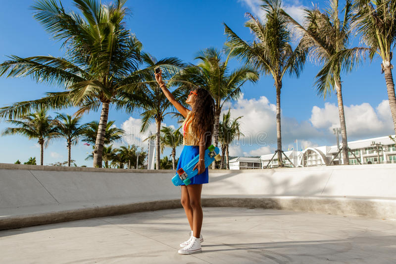 Beautiful teenage black girl in blue skirt take selfie with her. Outdoor lifestyle portrait of smiling black young woman in bright outfit. Hipster lady with royalty free stock image