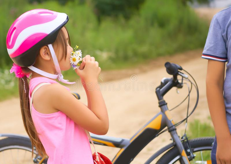 Beautiful teenage boy in protective bicycle helmet and girl in a park, boy giving flowers to the girl. Friendship stock photo