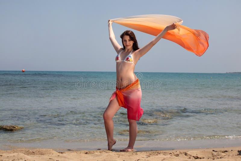 Beautiful teenage girl on the beach. Beautiful teenage girl on sandy beach holding up a wrap stock photo
