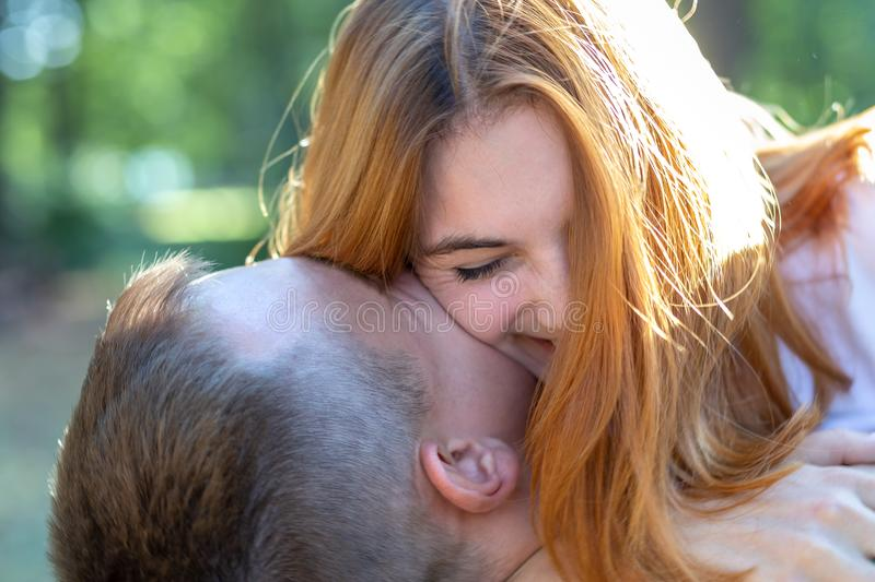 Beautiful teenage girl with bright red hair hugging her boyfriend outdoors. First love and romantic relationship concept.  stock photography