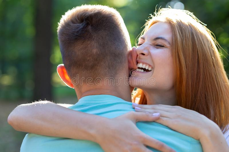 Beautiful teenage girl with bright red hair playfully biting her boyfriend by ear outdoors. First love and romantic relationship. Concept royalty free stock photography