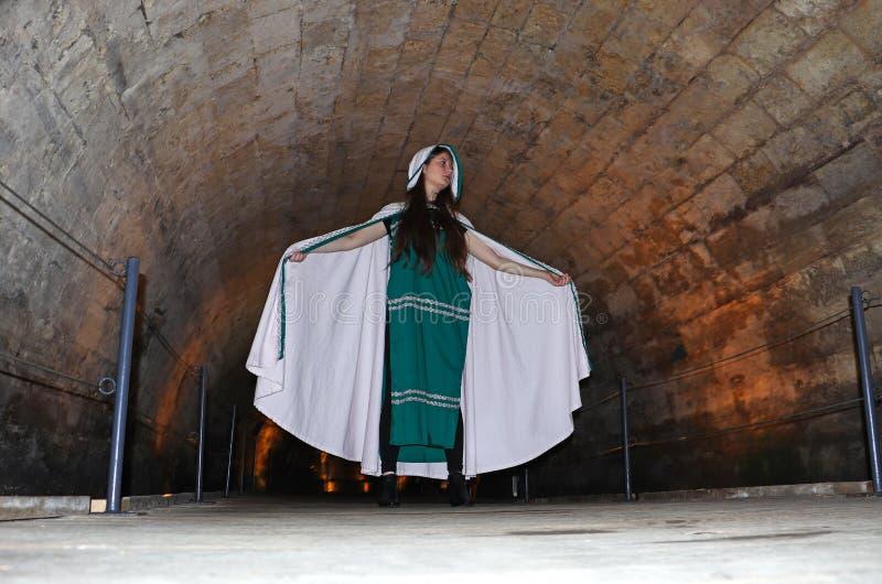 A teenage girl in the Templars tunnel in Akko, Israel. A beautiful teenage girl dressed as a Templar in the Templars Tunnel in Akko, Israel royalty free stock image