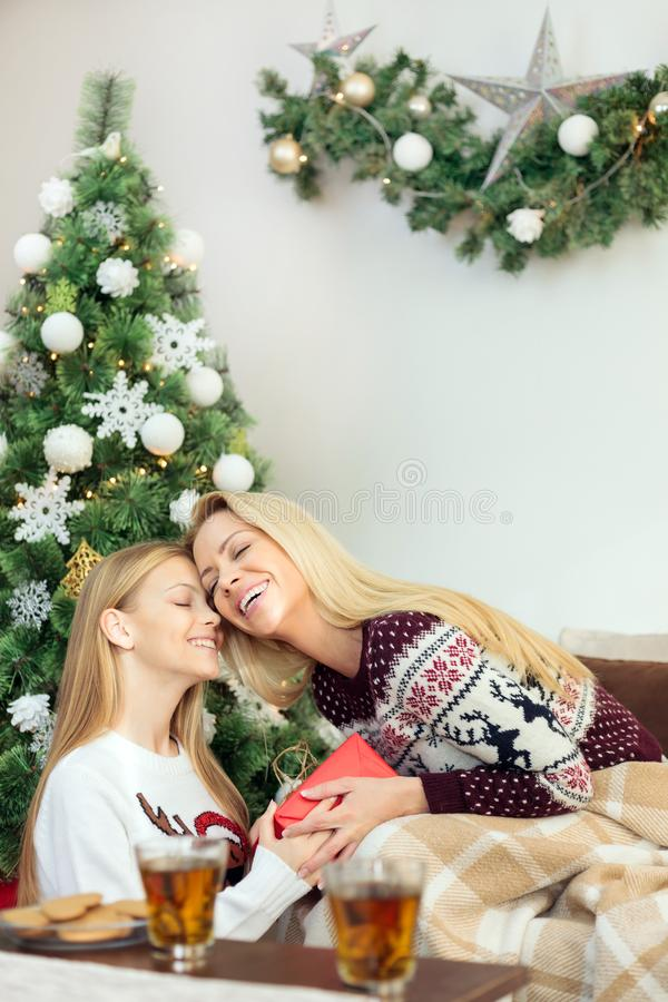 Beautiful teenage girl giving red gift box to her mother on a Christmas day. Single parent family celebrating Christmas at home and having a great time stock photo