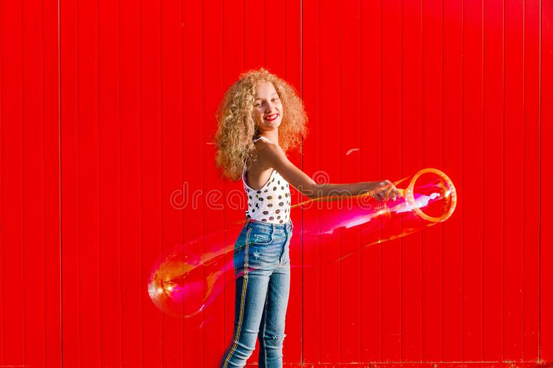 Beautiful teenage girl inflates soap bubbles against the red wall stock photography