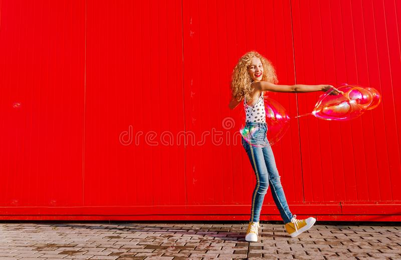 Beautiful teenage girl inflates soap bubbles against the red wall stock photo