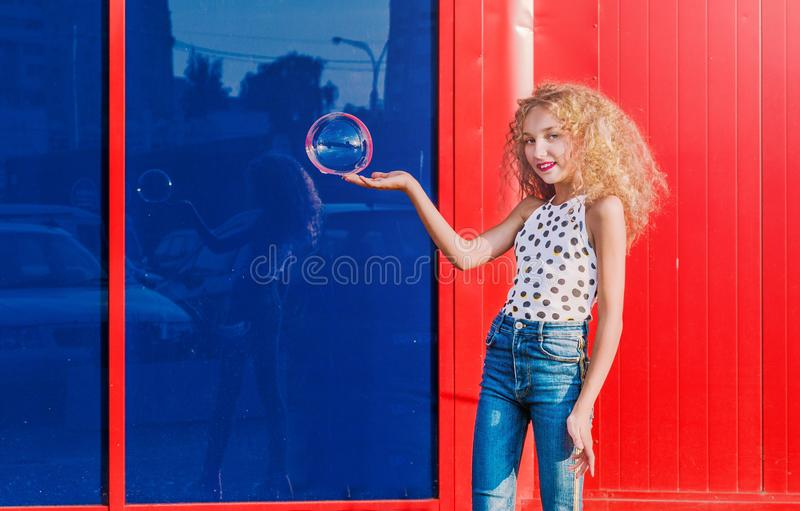 Beautiful teenage girl inflates soap bubbles in front of the red-blue wall royalty free stock image