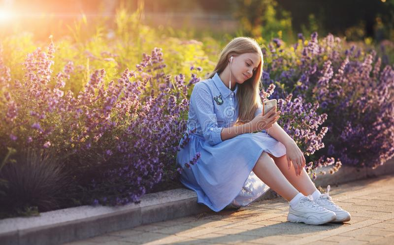 Beautiful teenage girl listening to music in headphones from smartphone. young happy model sitting outdoors in park flowers on stock image