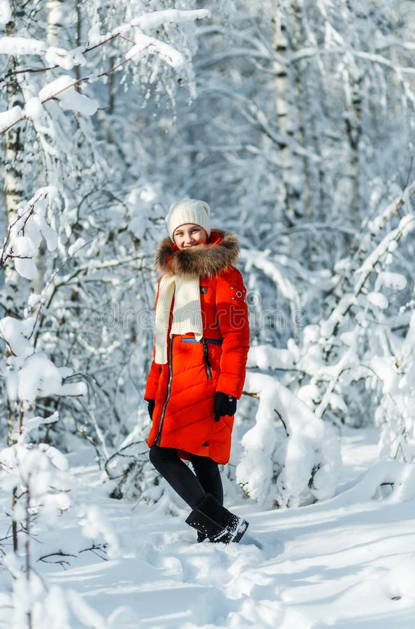 Beautiful teenage girl in a long red down jacket white hat and a scarf having fun outside in a wood with snow in winter stock image
