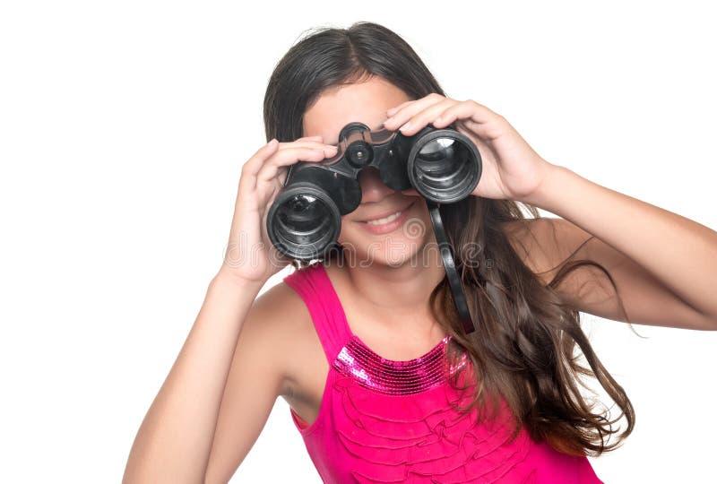 Beautiful teenage girl looking through binoculars stock photo