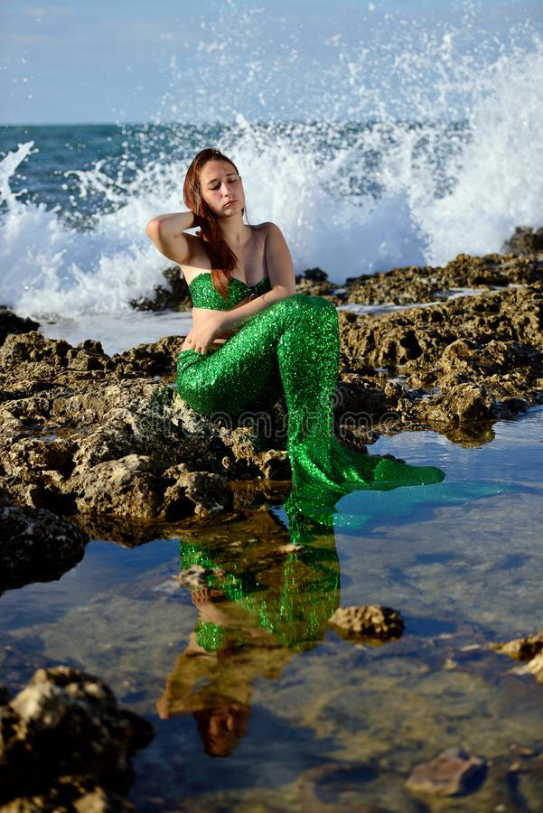 Teenage girl in a mermaid costume is sitting with her eyes closed on a rock on the beach against the backdrop of raging waves. royalty free stock photo