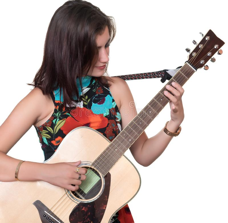 Beautiful teenage girl playing an acoustic guita isolated on white. Beautiful teenage girl playing an acoustic guitar - Isolated on a white background royalty free stock images