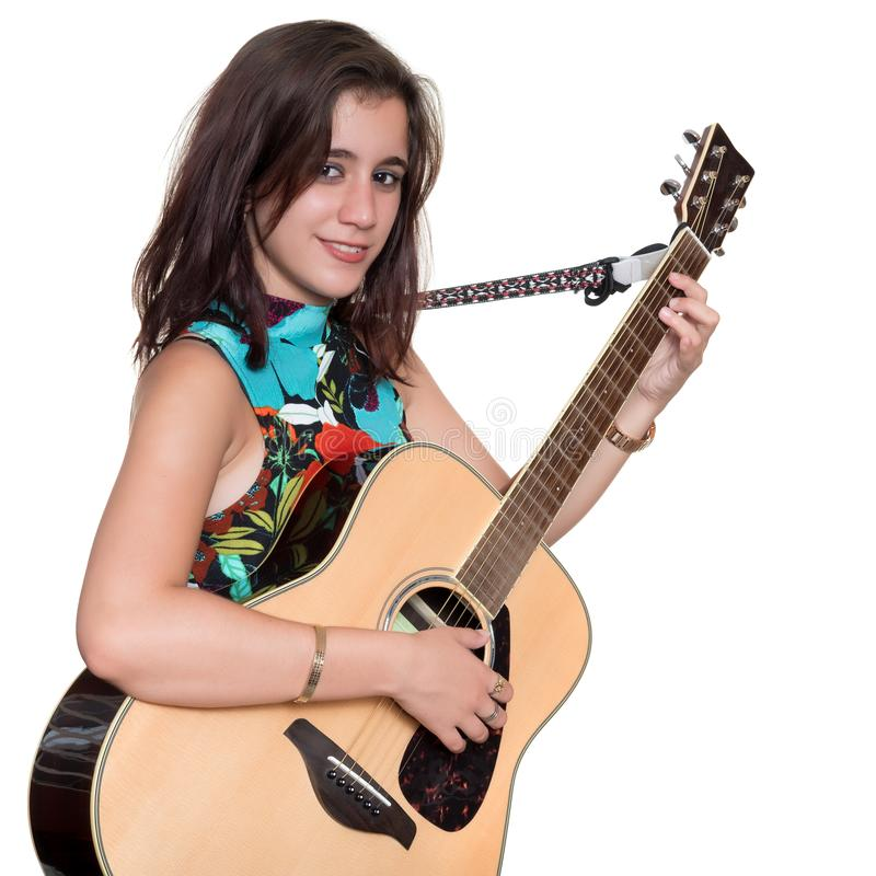Beautiful teenage girl playing an acoustic guita isolated on white. Beautiful teenage girl playing an acoustic guitar - Isolated on a white background royalty free stock photo