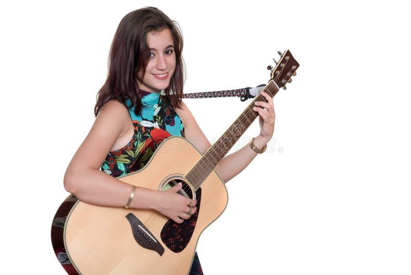 Beautiful teenage girl playing an acoustic guita isolated on white. Beautiful teenage girl playing an acoustic guitar - Isolated on a white background stock photo