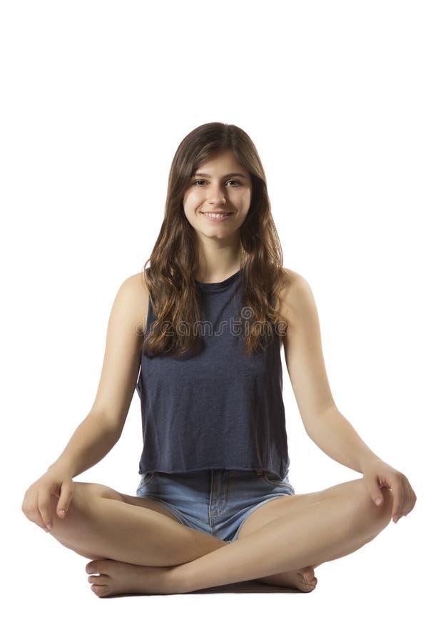 Beautiful teenage girl portrait sitting lotus position smiling. One beautiful teenage girl portrait sitting lotus position smiling happy in white background stock photos