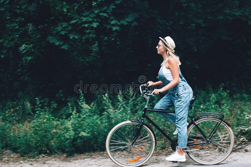 Beautiful teenage girl riding bicycle through the forest or park. stock images