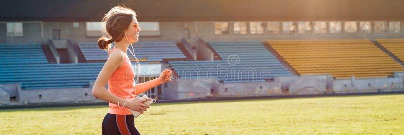 Beautiful teenage girl running in stadium, panoramic banner stock images