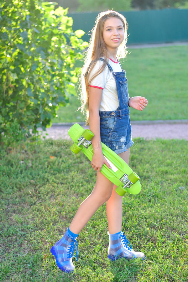 Beautiful teenage girl with skateboard in the green park in summer stock images