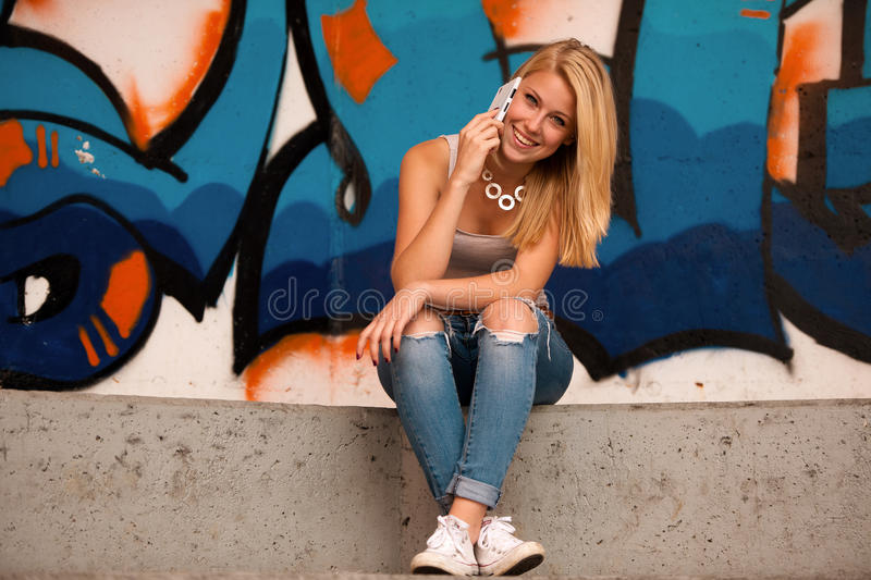 Beautiful teenage girl speaks on a cell phone outdoors royalty free stock photo